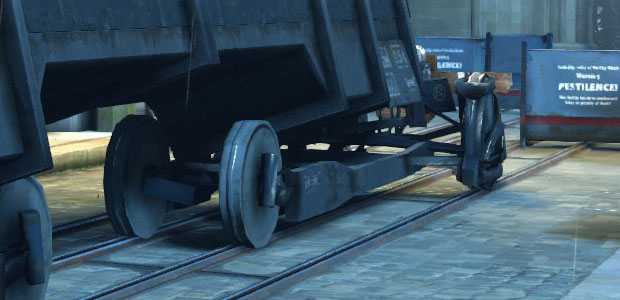 A train truck with the front wheels narrow and the rear wheels wide.